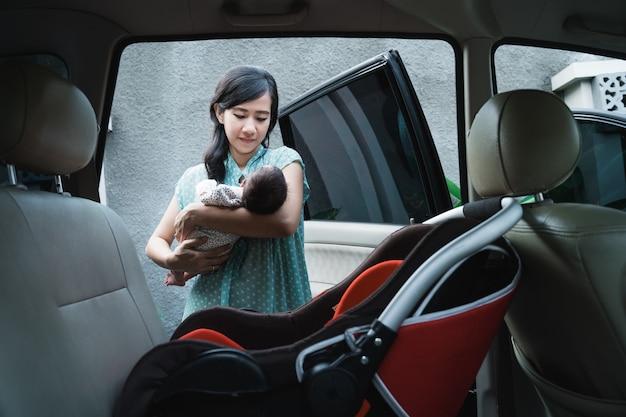 Młoda matka niosąca córkę przed włożeniem fotelika samochodowego