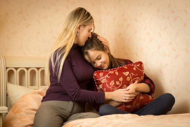 Młoda matka obejmuje i pociesza nastoletnią córkę w sypialni