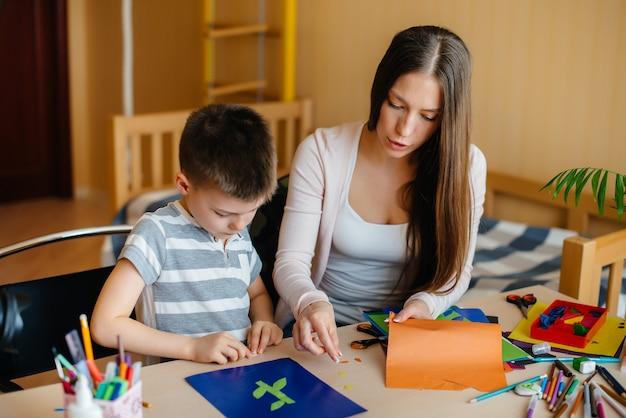 Młoda matka odrabia lekcje z synem w domu. rodzice i szkolenie