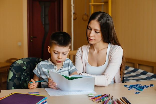 Młoda matka odrabia lekcje z synem w domu. rodzice i szkolenie.