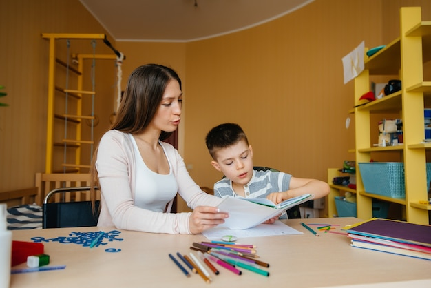 Młoda matka odrabia lekcje ze swoim synem w domu. rodzice i szkolenie.