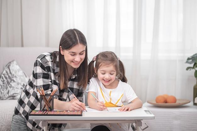 Młoda matka odrabia lekcje ze swoją małą uroczą córką. koncepcja domu i edukacji.