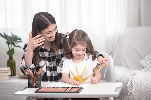 Młoda matka odrabia lekcje ze swoją małą uroczą córką. nauka w domu i edukacja