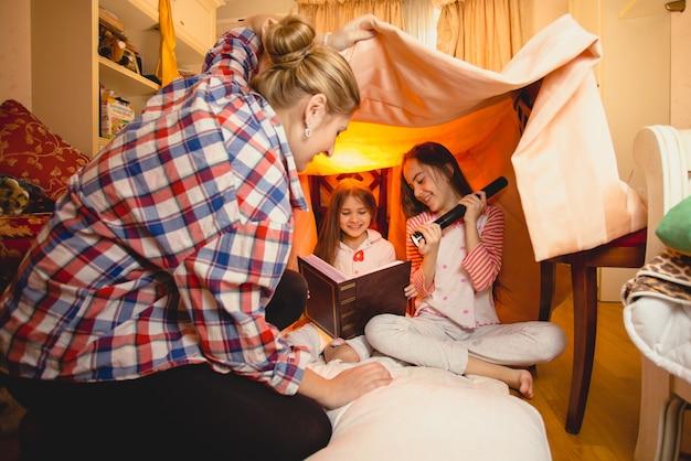 Młoda matka ogląda dwie córki czytające dużą książkę na podłodze w sypialni