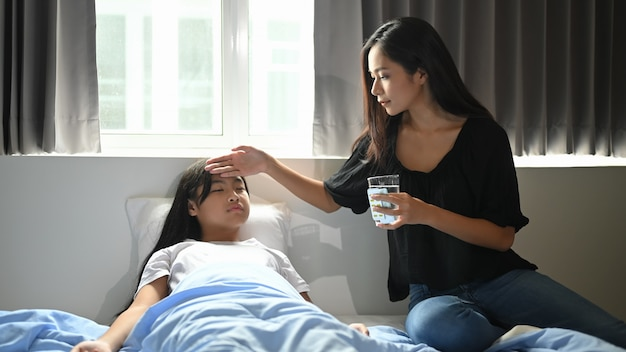 Młoda matka opiekuje się chorą córką w sypialni.
