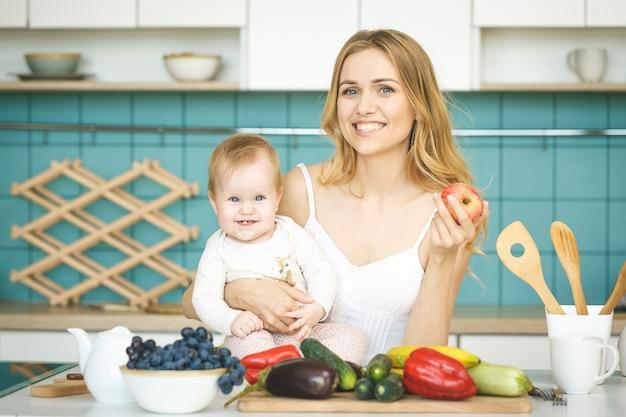 Młoda matka patrząc na kamery i uśmiechając się, gotując i bawiąc się z córką w nowoczesnej kuchni.