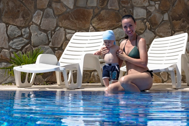 Młoda matka, piękna dziewczyna i dziecko w dmuchanym kręgu dla dzieci, w niebieskim basenie na wakacjach.