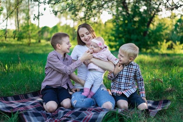 Młoda matka piknik w przyrodzie z trójką dzieci