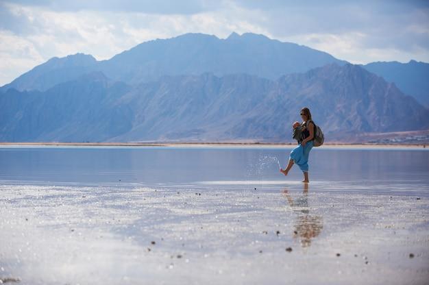 Młoda matka podróżuje na plaży z dzieckiem na temblaku