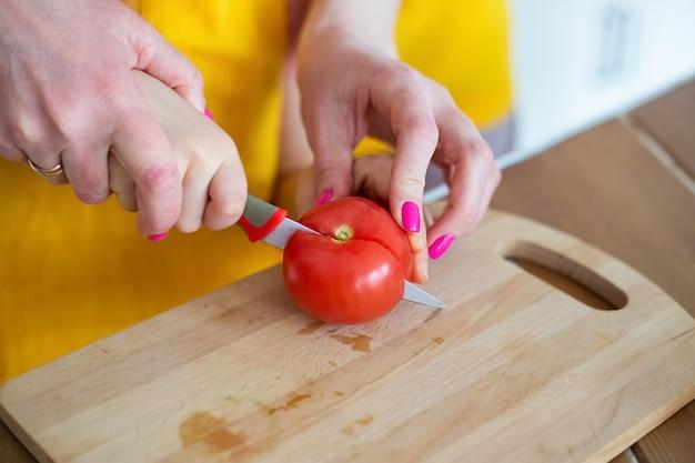 Młoda matka pomaga córce kroić pomidora nożem kuchennym na desce do krojenia
