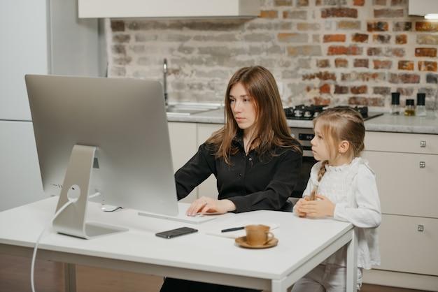 Młoda matka pomaga córce w odrabianiu prac domowych