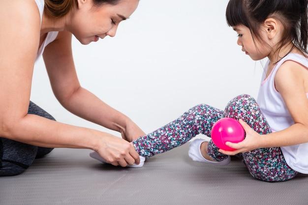 Młoda matka pomaga słodkie córki na sobie buty