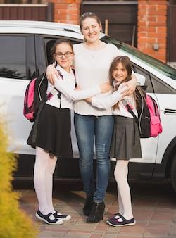 Młoda matka pozuje z córkami w plecakach obok samochodu