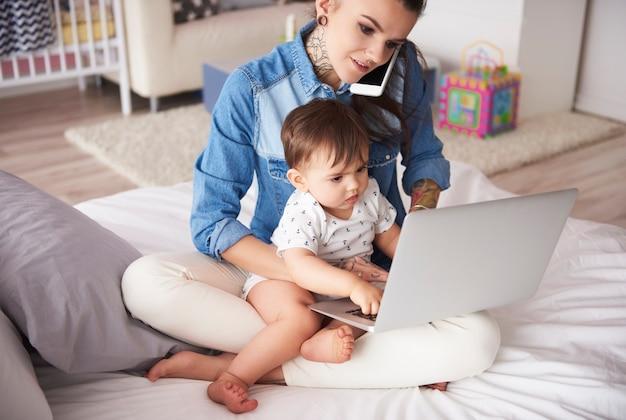 Młoda matka pracująca w domu z synem