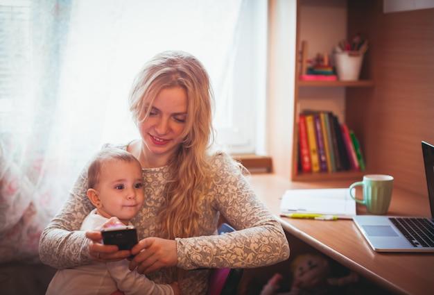 Młoda matka pracuje i trzyma córkę w ramionach
