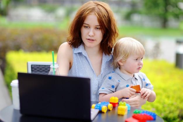 Młoda matka pracuje oh jej laptop i trzyma jej smutnego malucha syna