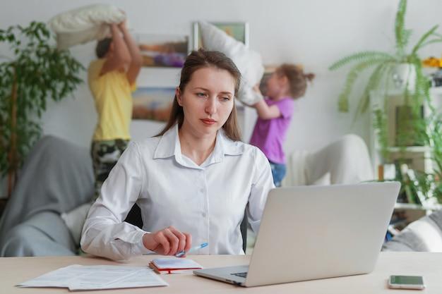 Młoda matka pracuje w domu z laptopem, dzieci zakłócają pracę zdalną.