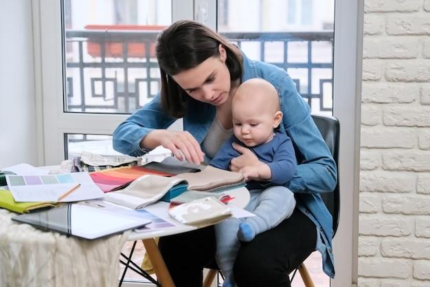 Młoda matka pracy z dzieckiem w ramionach w domowym biurze. kobieta projektantka wnętrz pracująca z próbkami tkanin, na tablecie stołowym, szkicami i paletami tekstylnymi