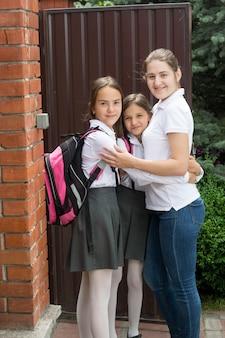 Młoda matka przytula córki przed ich wyjściem do szkoły