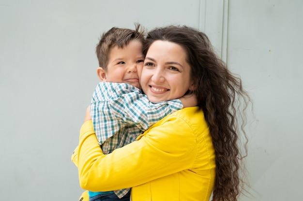 Młoda matka przytula dziecko w ramionach.