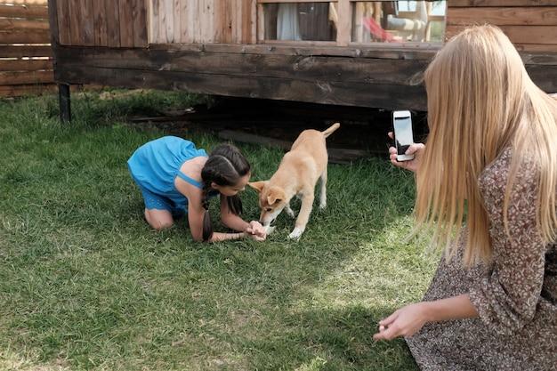 Młoda matka robi zdjęcie na jej telefon komórkowy, podczas gdy jej córka bawi się z psem na zewnątrz
