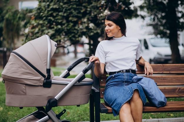 Młoda matka siedzi na ławce w parku z wózkiem dziecięcym