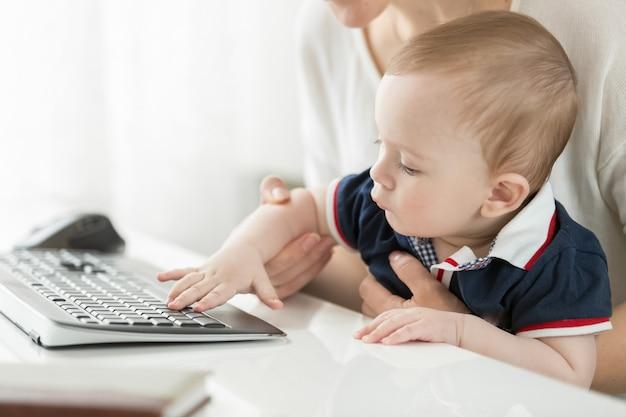 Młoda matka siedzi przy komputerze i trzyma swoje dziecko na kolanach