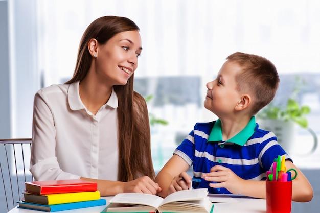 Młoda matka siedzi przy stole w domu, pomagając jej małego syna ze swoją pracą domową ze szkoły