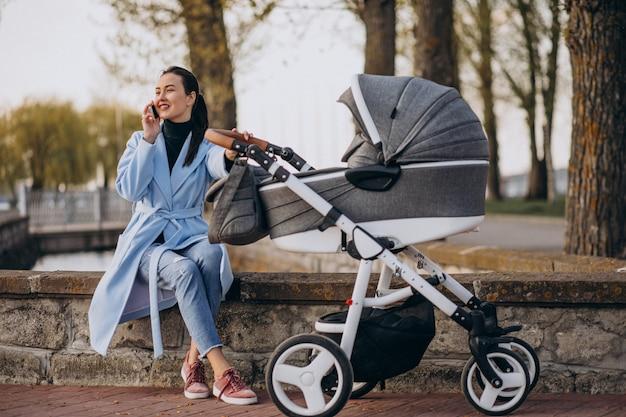 Młoda matka siedzi z wózek w parku