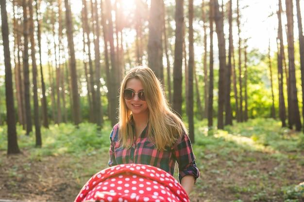 Młoda matka spaceru i pchania wózka w parku. matka spacerująca z noworodkiem. piękna szczęśliwa matka z wózkiem na zewnątrz. letnie spacery w słoneczny dzień. dziewczyna z bryczką.
