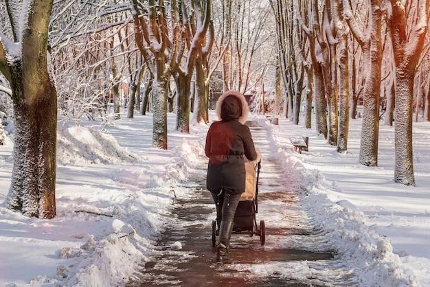 Młoda matka spaceru z wózkiem dziecięcym w winter park. dziewczyna z wózkiem jedzie na drogę zimą. śnieżna aleja leśna.
