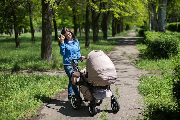 Młoda matka spacerująca i pchająca wózek w parku