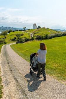 Młoda matka spacerująca z synem ścieżką w parku przyrody saint jean de luz zwanym parc de sainte barbe, col de la grun we francuskim kraju basków