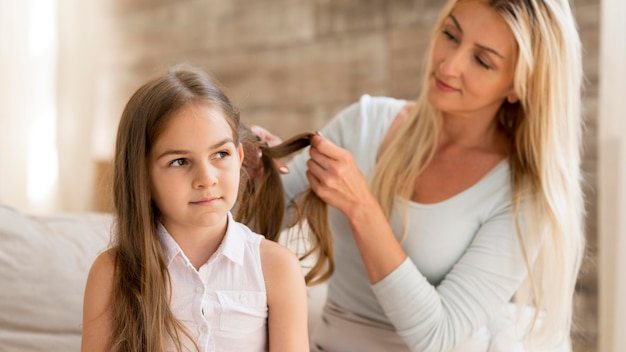 Młoda matka splatająca córce włosy w domu