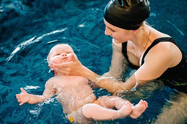 Młoda matka, szczęśliwa mała dziewczynka w basenie. uczy niemowlę pływać. ciesz się pierwszym dniem kąpieli w wodzie. mama trzyma dziecko przygotowuje się do nurkowania. robienie ćwiczeń. ręka prowadzi dziecko na wodzie