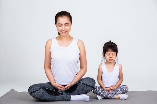 Młoda matka szkolenia urocza córka z jogą