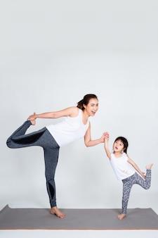 Młoda matka trenuje uroczą córkę z gimnastycznym