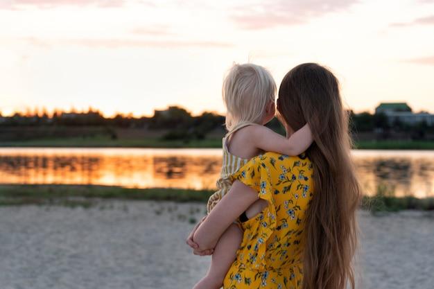 Młoda matka trzyma dziecko i ogląda zachód słońca nad wodą.
