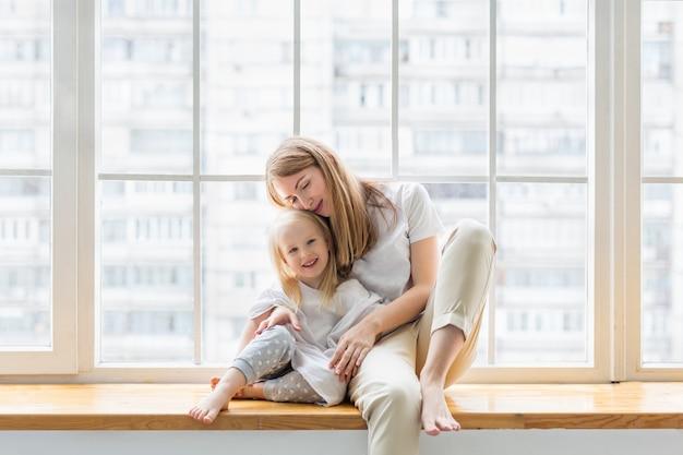 Młoda matka trzyma jej 3,5 letnią córkę siedząc na parapecie.