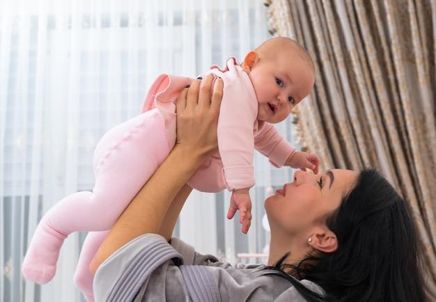 Młoda matka trzyma swoje dziecko nad głową i cieszy się, patrząc na nią. dziecko ubrane jest w różową piżamę i patrzy w kamerę, unosząc się nad twarzą kobiety