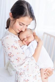 Młoda matka trzyma w ramionach noworodka i kładzie je spać w sypialni przy łóżeczku, koncepcja macierzyństwa i szczęśliwej rodziny