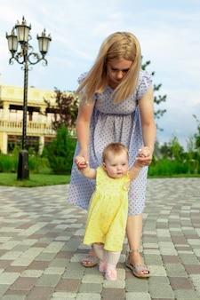 Młoda matka uczy córeczkę spacerować z dzieckiem w parku latem, szczęśliwe macierzyństwo, pierwsze kroki
