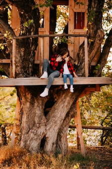 Młoda matka w czerwonej koszuli z córką w domku na drzewie