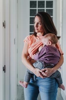 Młoda matka w domu karmi piersią swoją uroczą roczną dziewczynkę.