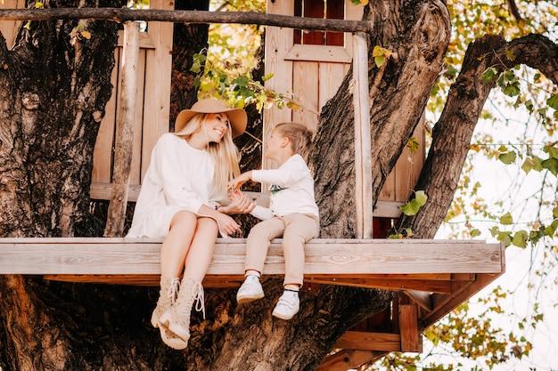 Młoda matka w kapeluszu i białej sukni z synem w domku na drzewie.
