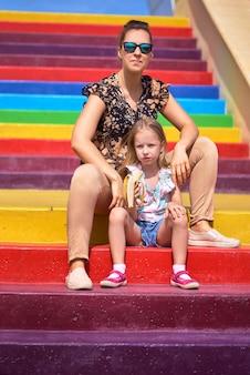 Młoda matka w okularach i córka siedzą na kolorowych schodach. pojęcie ochrony dziecka, dzień matki