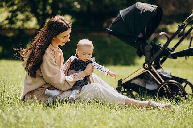 Młoda matka w parku z dzieckiem siedzi na trawie