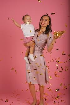 Młoda matka w różowej sukience trzyma w ramionach swojego małego synka na przyjęcie z konfetti