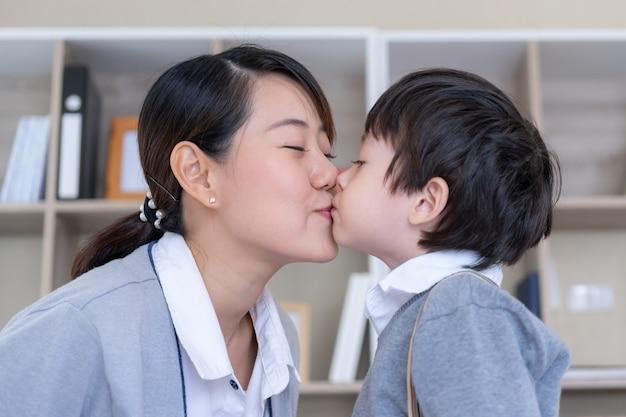 Młoda matka wesoła z małym chłopcem całuje jej policzek w sypialni