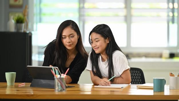 Młoda matka wraz z córką siedzi i odrabia lekcje przy drewnianym stole